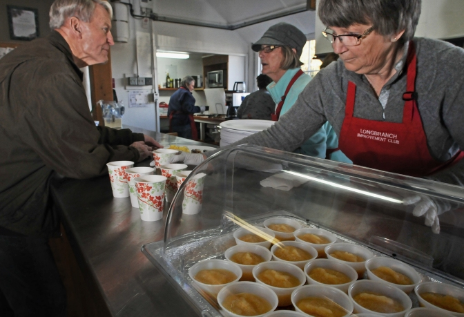 Barb Van Bogart, right, working behind the kitchen counter at the Longbranch Improvement Club's pancake breakfast fundraiser Saturday.