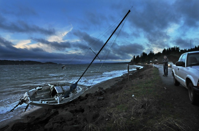 Tim Sterling watches his sailboat that the strong winds blew off its anchors on Henderson Bay and beached on the Purdy sand spit early.