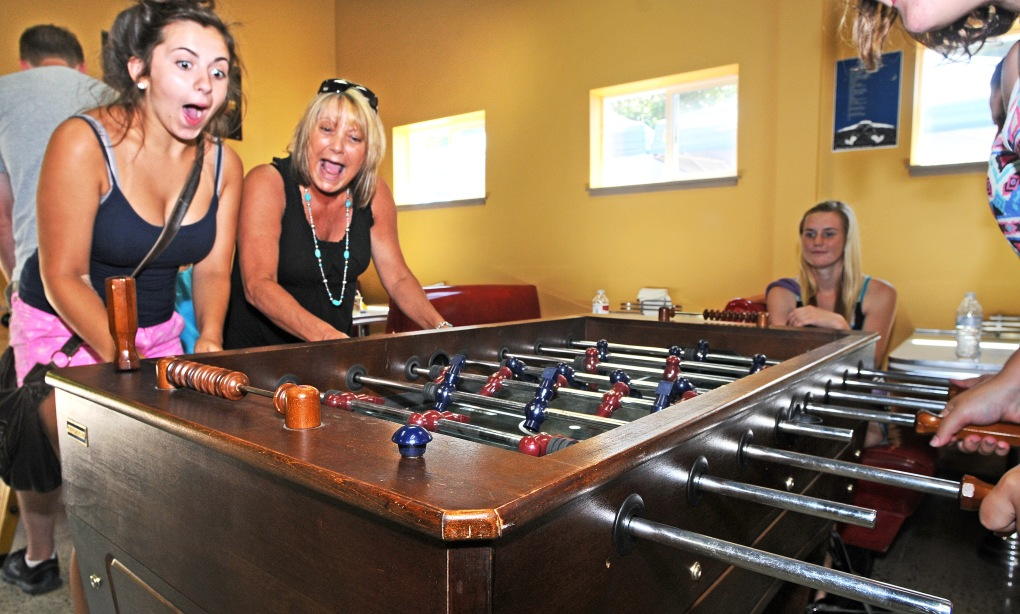 Hannah Baker, left, who is visiting from Albany, Ore., enjoy a spirited game of foosball with her aunt and friends Aug. 10 during the Red Barn's community open house.