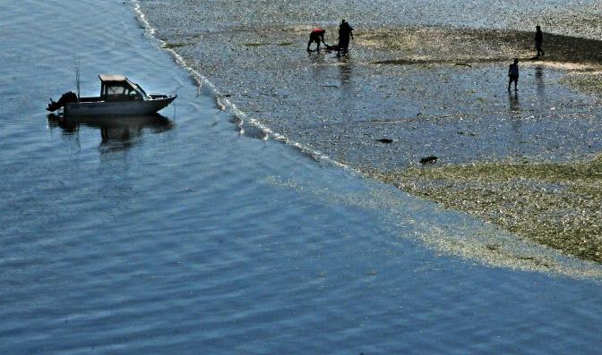 A group on a small boat enjoys the bounty of the sandbar after the sun finally made an appearance.