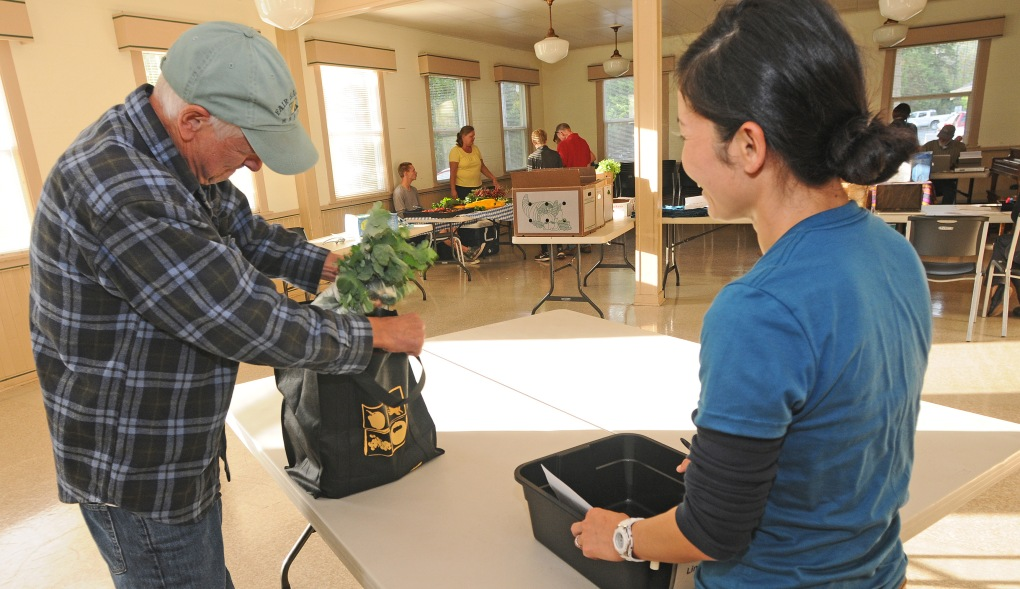 Cooperative volunteer Jungko Jacobsen, right, helps a Steve Berry with his order.