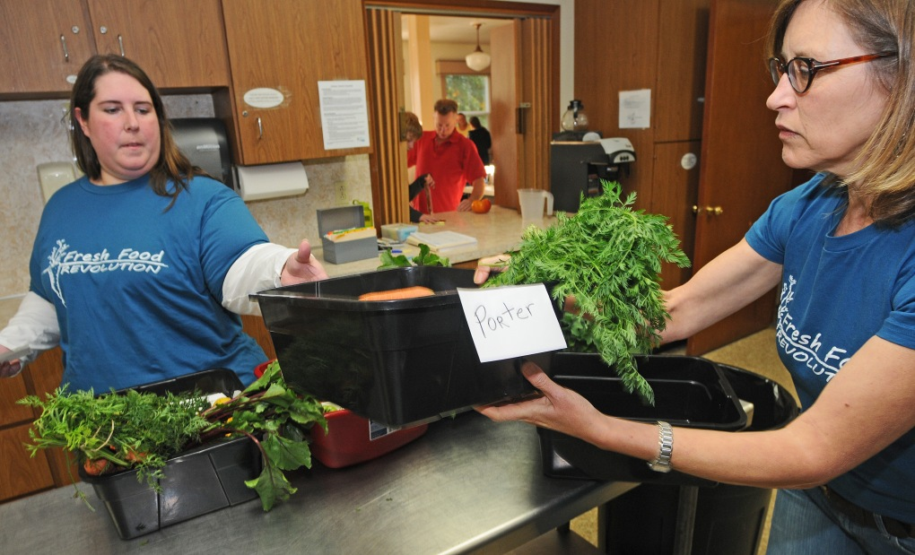 Lisa Bryan, right, and Candy Clark help find the produce order for a member of the cooperative.
