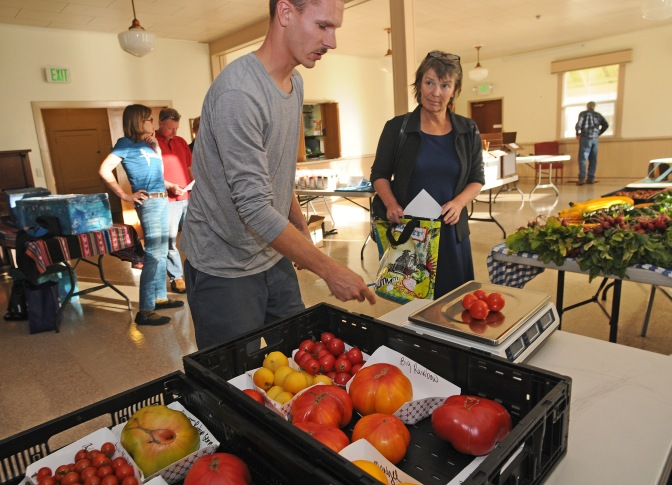 Sam Boucher, left helps Edie Morgan with her purchase at the Fresh Food Revolution cooperative market at the Key Peninsula Civic Center Wednesday (Oct. 1).
