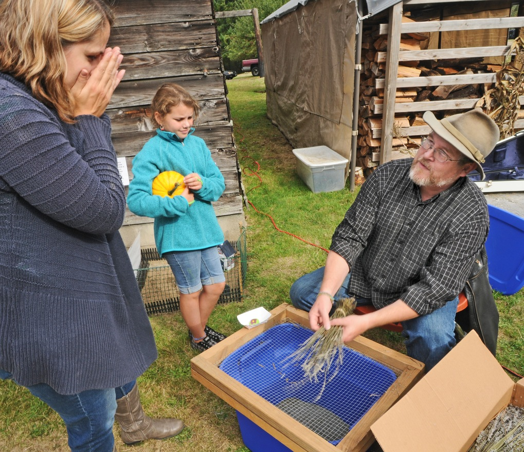 Philip Marshall, right, demonstrate to Beth Stitt, left, and her daughter Zoe how to strain the buds of a lavender. Stitt smells her hands after handling the aromatic stems.