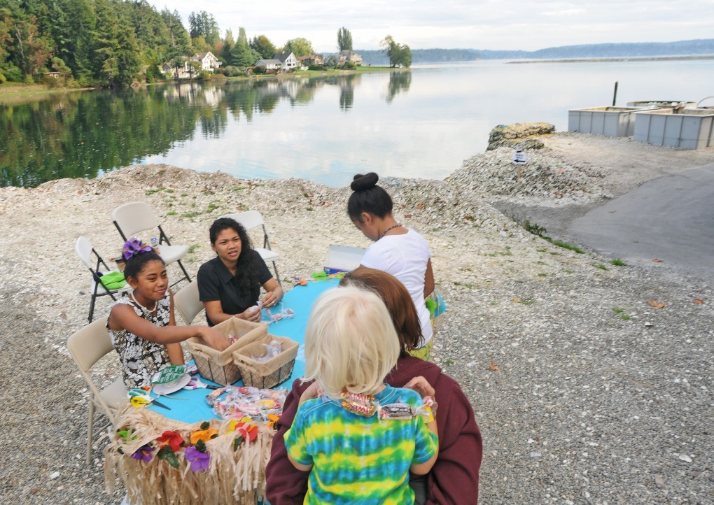 Tai Mamea, middle, who does accounting work at Minterbrook Oyster Farm, and her two daughters Kiki, right, and Malaysia greeted guests of the KP Farm Tour with candy leis Saturday.
