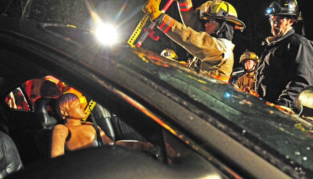 Marc Beal, right, shows a volunteer firefighter how to use a regular auto jack to pry open a car window.