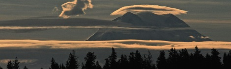 Strips of clouds drift by Mount Rainier at sunrise Monday Spet. 29, 2014.