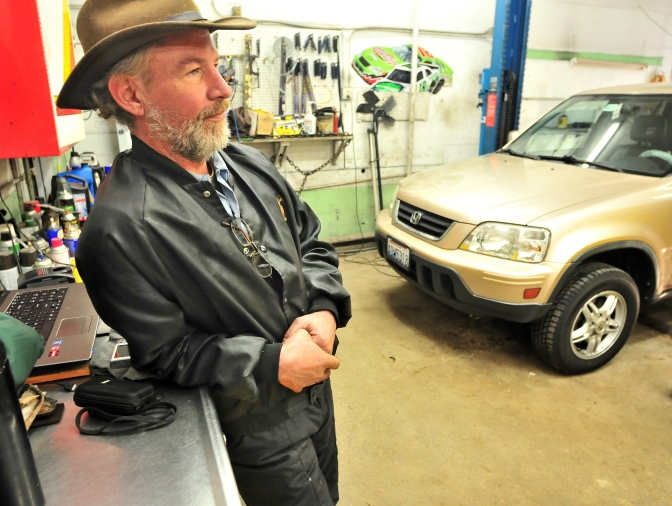 Jon Goods, 50, of Wauna, waits for customers to drive up to the Northwest Auto Clinic.