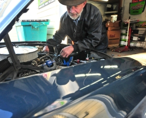 Goods checks the newly rebuilt engine of a navy blue 1967 Mustang at the Northwest Auto Clinic in Wauna Thursday.