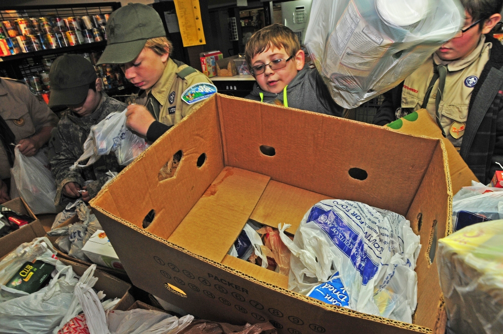 Ben Going, 12, left, Crason Helland, 11, middle, and Zach Wedel, 12, right help sort the bags of food donations at the Key Peninsula Community Services Food Bank.