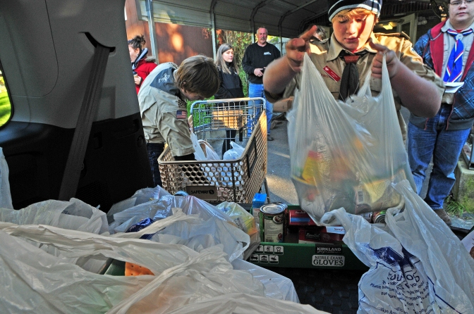 Max Goins help unload food from the back of an SUV. Programs like this helps the food bank collect more than $570,000 worth of food each year.