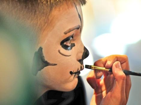 Kobe Niz, 7, get his face painted in a skeletal pattern by Jackie Baltmiskis.