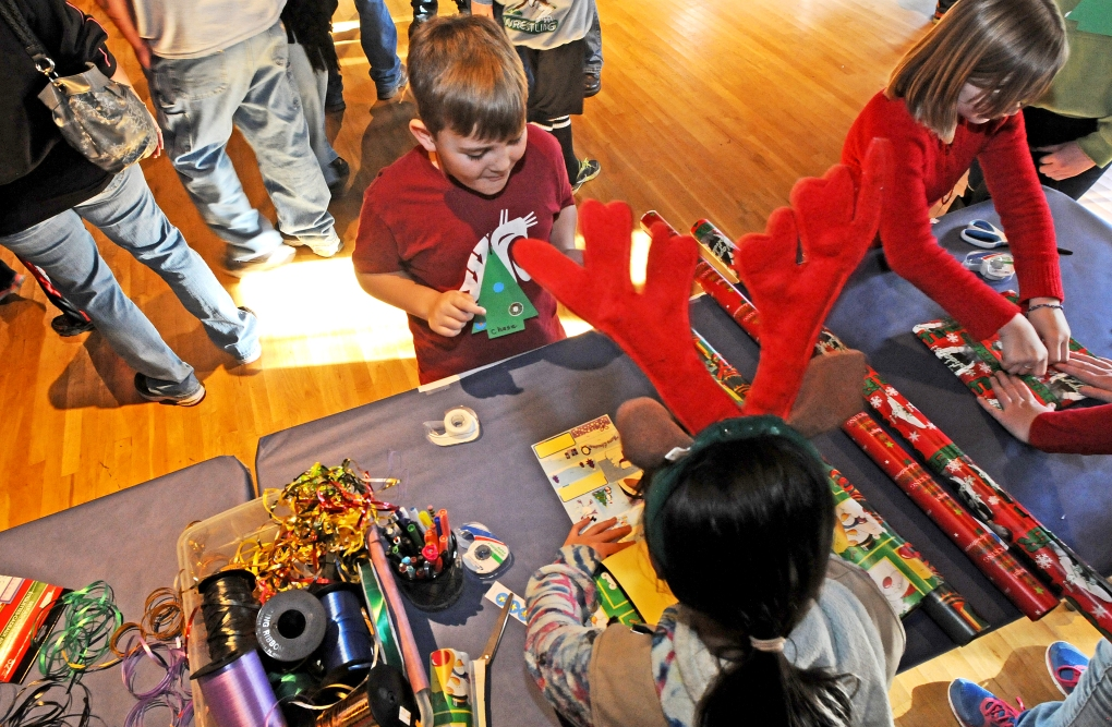 Mate Greenatck, 12, with reindeer antlers, helps Chase Midway, 9, wrap a present for Midway's cousin Conner.