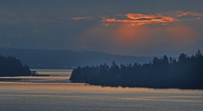 The sun peeking through the morning coastal fog hanging over the South Sound Saturday reflecting dramatic light on Drayton's Passage..