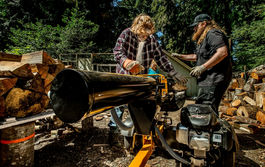 Larry Henderson and his son Shane fire up the log splitter that he bought with the money he received from a Spark Grant through the Greater Tacoma Community Foundation.
