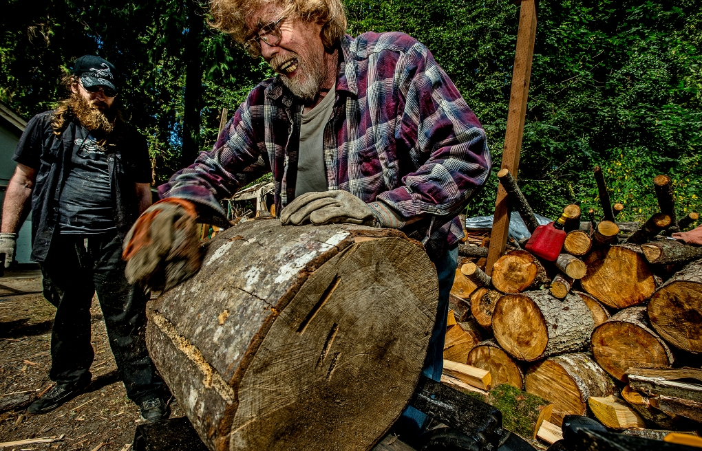 Larry Henderson preps a round for the log splitter. They have given out more than 120 cords of wood since they started the program, he said, asking only for a $15 donation to cover the cost of fuel. Henderson delivers the wood himself in his old pickup truck.