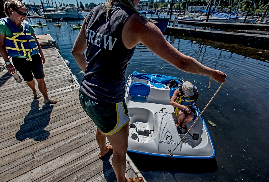 A crew member at the boat rental place by the Peninsula Yacht Basin helps my lovely bride aboard the paddle boat.