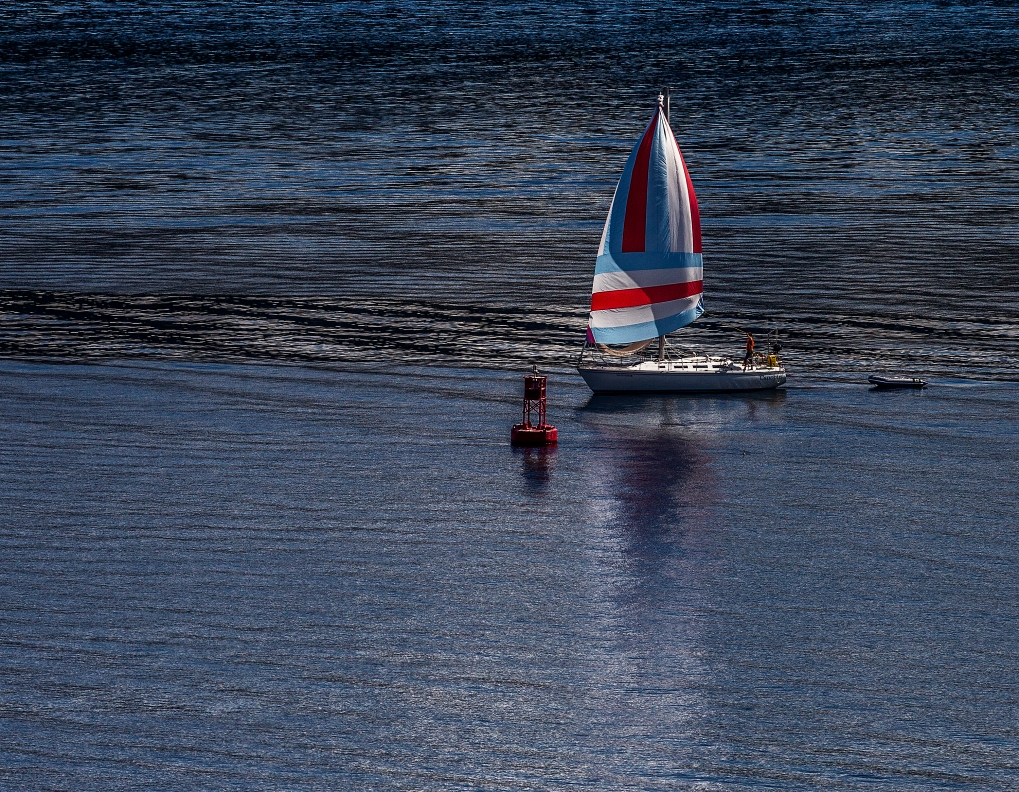 A sailboat approaches the buoy by the sandbar Monday afternoon.
