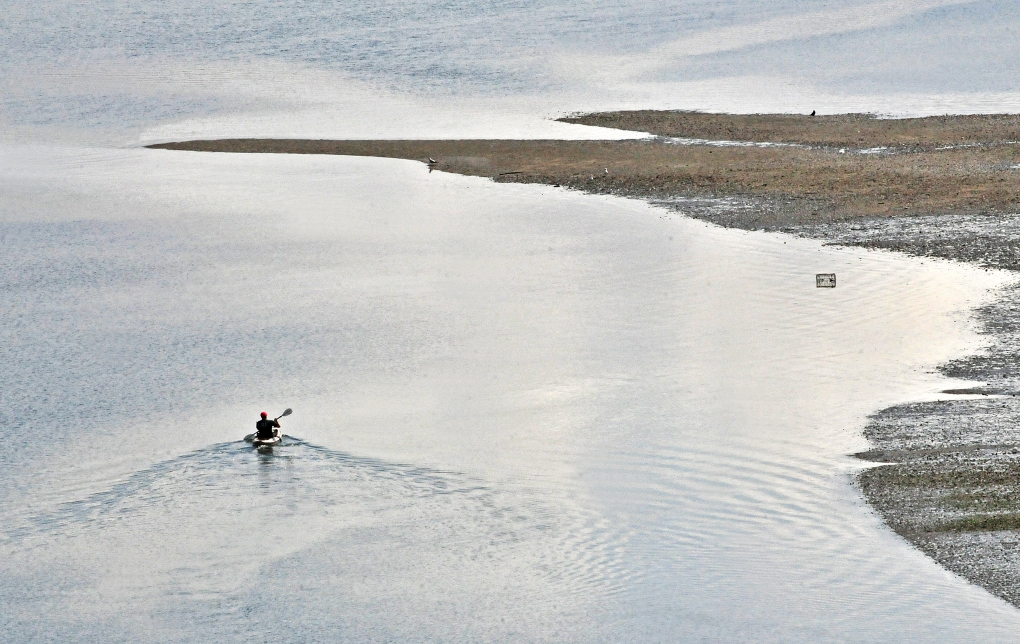 A kayaker paddles up to the sand bar near the tip of the Key Peninsula in Longbranch, Washington, April 4, 2015. It was another beautiful spring day, mostly sunny with the hig in the mid 50s.