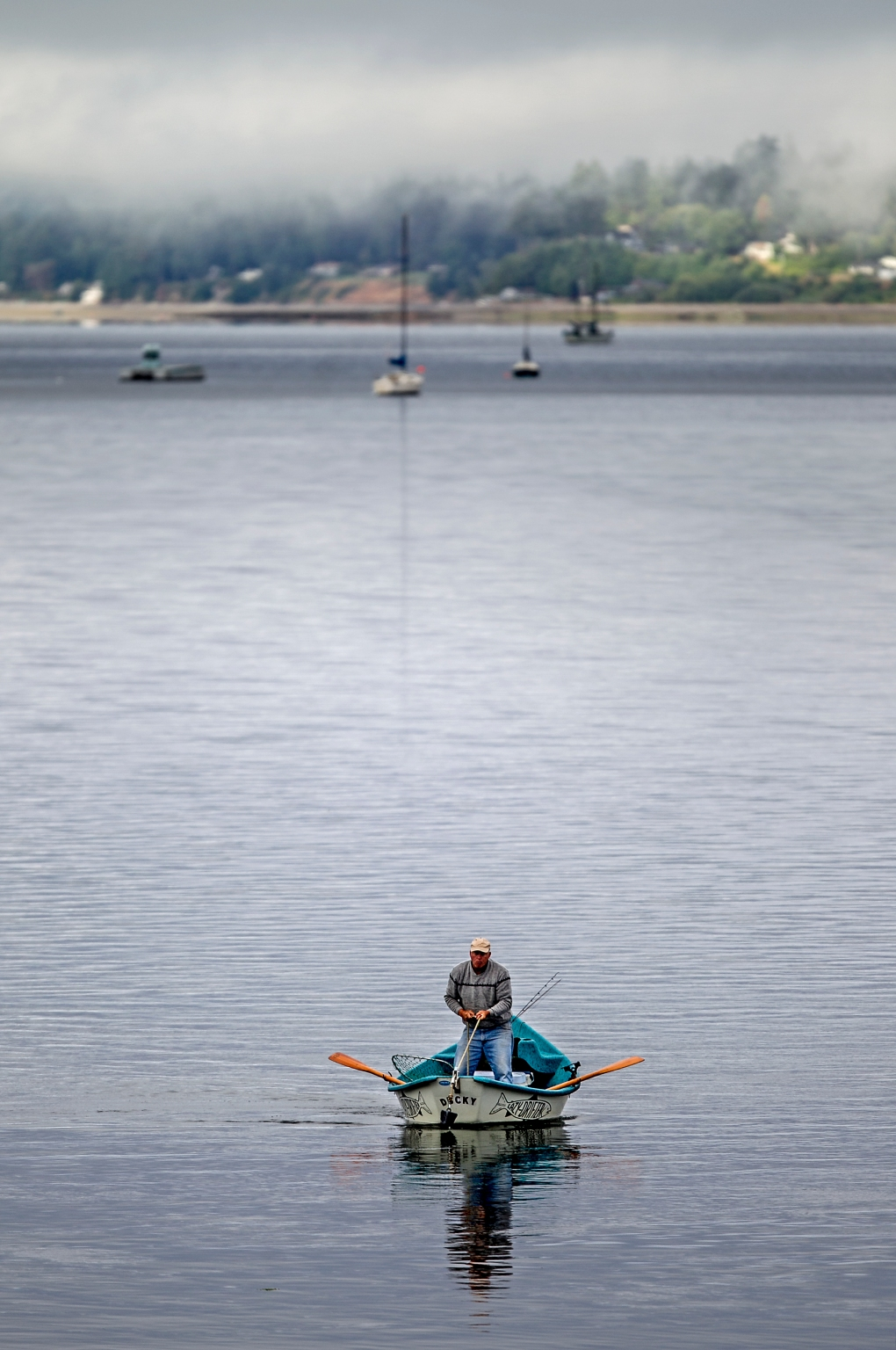 A fisherman in a rowboat pulls up anchor on Henderson Bay in Gig Harbor, Washington, Monday morning July 27, 2015. The forecast from the National Weather Service calls for partly cloudy skies and a high of 75 degrees.