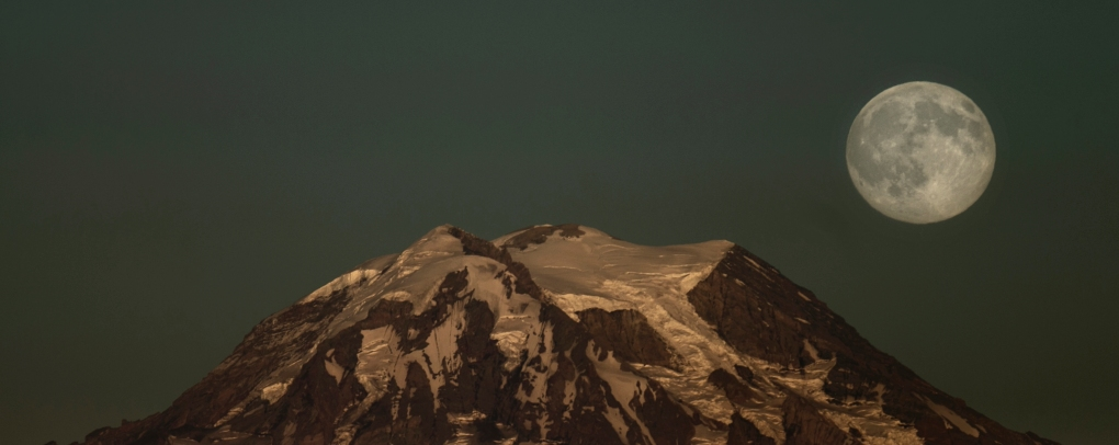 "The moon rises over Mount Rainier seen from Longbranch on the eastern shore of the Key Peninsula Thursday July 30, 2015. For the second time this month, the Moon is about to become full.  There was one full Moon on July 2nd, and now a second is coming tomorrow.  The science.nasa.gov website says that according to modern folklore, whenever there are two full Moons in a calendar month, the second one is ""blue."""